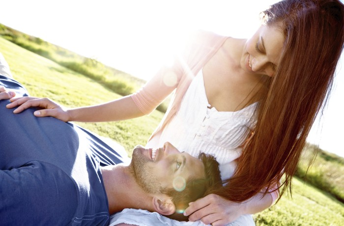 A couple in a field with the boyfriend lying his girlfriend's lap while they share an intimate moment